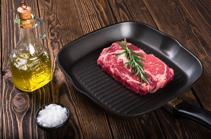 Raw marbled meat steak Ribeye on grill pan on dark wooden background