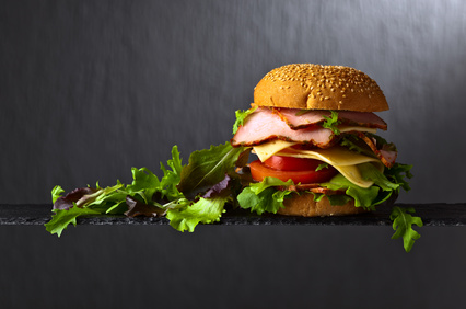 burger with ham and salad on a dark background