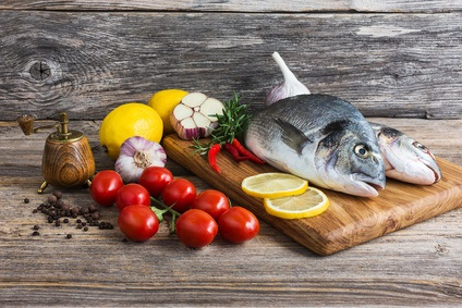 Raw fish with vegetables, ready to cook. Dorada fish