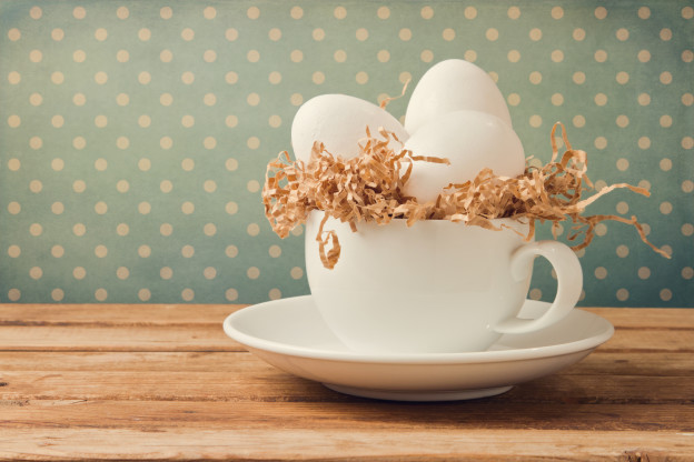 Retro still life with eggs and coffee cup over background with polka dots
