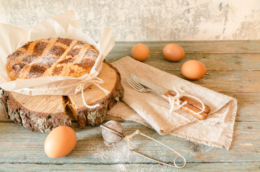 Neapolitan Easter cake with ricotta and wheat on old wooden table. Next egg, knife and fork. Rustic style.
