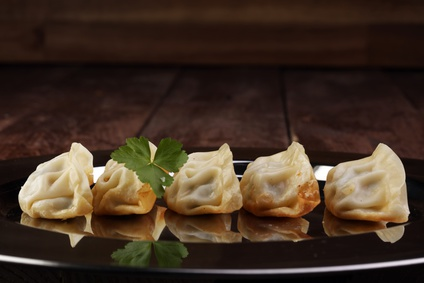 A plate of Japanese gyoza dumplings sitting on a rustic wooden table.